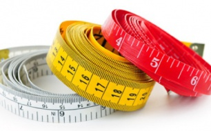 Three colorful measuring tapes coiled on white background